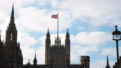 the union jack flies above westminster parliament house in london, england