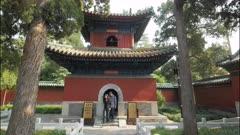 tourists inspect a bell tower inside beihai park in beijing, china