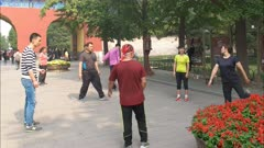 players involved in a game of jianzi, similar to hacky sack, at the temple of heaven, in beijing china