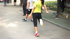 close up of a player involved in a game of jianzi, similar to hacky sack, at the temple of heaven in beijing, china