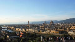 tourists admire the evening  view of the duomo and florence from piazzale michelangelo