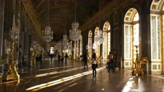 sunlight streams into the dazzling hall of mirrors in the palace of versailles