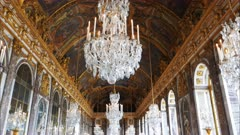 a wide gimbal shot of the ceiling of the opulent hall of mirrors in the palace of versailles, paris