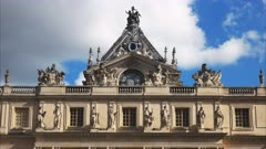 a view of the statues and ornate architectural detail on the roof of the palace of versailles, paris france