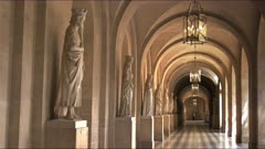 a zoom in shot of a covered walkway with marble statues at the palace of versailles, paris france