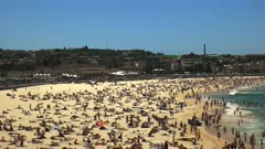 panning right shot of summer crowds at bondi beach, australia's most famous beach
