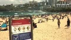 the view looking south of sydney's bondi beach and an information sign