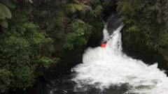 a kayaker takes on tutea falls on kaituna river near rotorua, new zealand