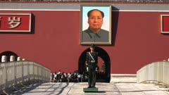 close up shot of the portrait of mao and a soldier on duty at the entrance to the forbidden city at tiananmen square, beijing