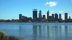 a kayaker enjoys a morning paddle on western australia's swan river, with the city of perth in the background