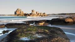 a view of seaweed covered rocks and the granite picnic rocks on the east coast of tasmania, australia