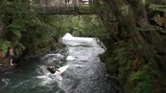 young male tourists use a surfboard and rope to have fun on kaituna river near rotorua, new zealand