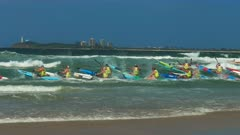 tracking shot of surf ski competitors leaving the beach in a race at the 2016 aussies
