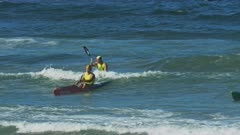 several competitors paddle in to finish a surf life saving surf ski race on the sunshine coast of australia