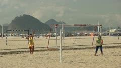 60p slow motion shot of a woman serving in a  beach tennis game on copacabana beach in rio de janeiro, brazil
