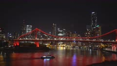 night shot of a ferry and brisbane's story bridge illuminated by red lights as seen from from bowen terrace