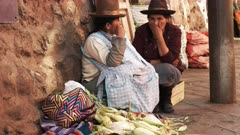 two women talk while selling corn at a street market in cusco, peru