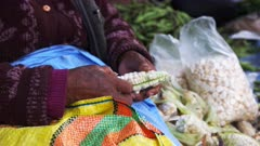 side on view of a peruvian woman taking giant corn kernels of the cob at a street market in cusco, peru