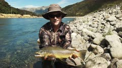 a fly fisherman poses with a large live new zealand brown trout prior to it being released