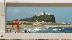 nobbys head in newcastle, australia framed by fence railings