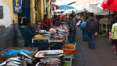 wide view of fishmongers selling fresh fish at a street market in cusco, peru