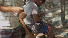 close up of fishermen mending nets on copacabana beach in rio de janeiro, brazil
