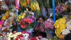 a woman trims a rose flower at san pedro market in cusco, peru