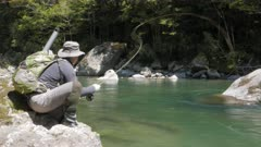 low angle shot of an fly fisherman hooking a trout on the maruia river in new zealand