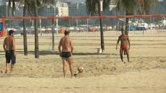 a player kicks off and point is played in a footvolley game on copacabana beach in rio de janeiro, brazil