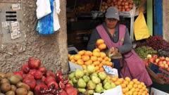 a woman bags fresh mandarins at a market in cuzco, peru