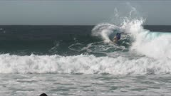 a surfer performs a series of cutbacks on a gold coast wave in queensland, australia