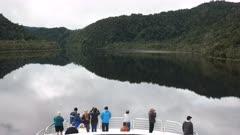 tourists on the bow of a boat enjoying a gordon river cruise in tasmania, australia