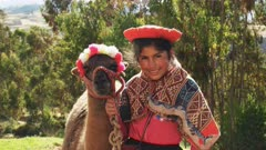 a peruvian girl in traditional dress poses for tourists with a llama to earn money near ollantaytambo, peru