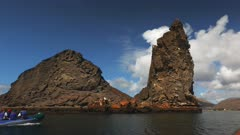 the view of pinnacle rock and a zodiac dinghy with tourists at isla bartolome in the galapagos