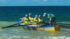a men's surf boat crew battle to get through the waves at the start of a race on the sunshine coast of australia
