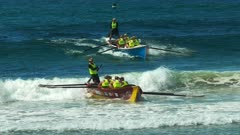 high angle close up of two surf boats catching waves at the end of a race during a surf life saving carnival