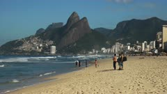 a group of surfers watch the waves at ipanema in rio de janeiro, brazil