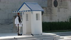 guard in dress uniform beside a sentry box at the parliament in athens, greece