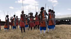 wide view of a group of maasai boys dancing at  koiyaki guiding school, kenya