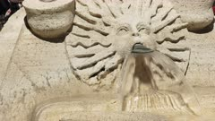 water flowing from a sun-shaped human face on the ugly boat fountain at the spanish steps in rome, italy