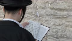 close up of a jewish man worshiping with a prayer book at the western wall in jerusalem, israel