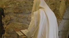 a jewish man in a prayer shawl worships at the wailing wall in jerusalem, israel
