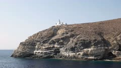 tracking shot of lighthouse on a greek island in the mediterranean sea from an interisland ferry