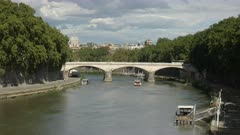 afternoon view of a tour boat approaching a bridge across the tiber river in rome, italy