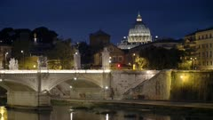 night shot of the dome of st peter's basilica and tiber river in rome, italy