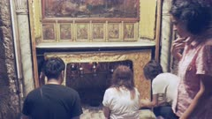 three whorshipers kneel at the star in the church of the nativity in bethlehem