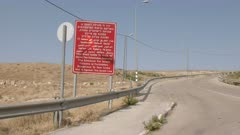 zoom in shot of an entry sign by the side of a road to the palestinian territory
