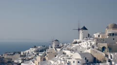 afternoon shot of whitewashed houses and windmills at oia on the island of santorini, greece