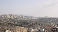 panning shot of israeli settlements in the disputed palestinian territory as seen from bethlehem