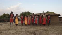 wide view of a group of maasai women and men singing at a village in kenya